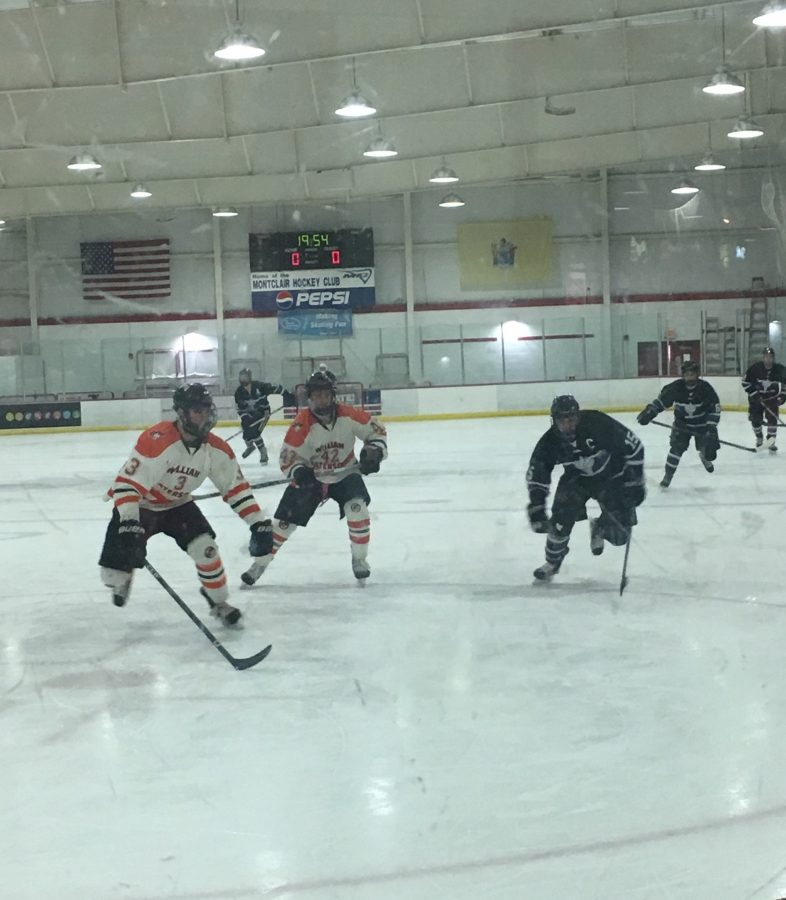 First period action as skaters chase the puck in the William Paterson defensive zone. Left to right: Ryan Melvin, Edmund Coxe, and NYU captain Steve Esposito