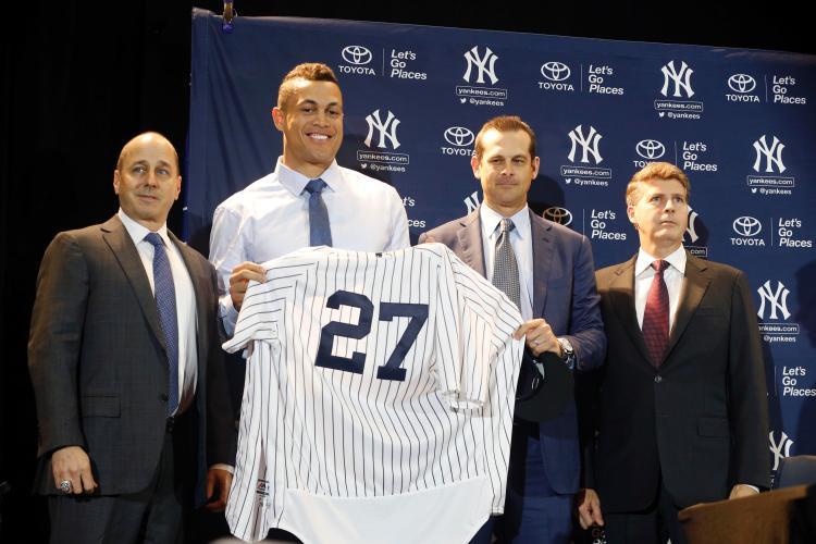 Giancarlo Stanton was introduced as the newest member of the New York Yankees Monday, alongside general mananger, Brian Cashman (left), manager Aaron Boone and owner Hal Steinbrenner. (Via nydailynews.com)